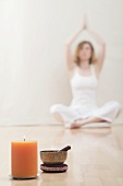 Young woman meditating, candle and singing bowl