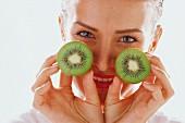 Woman with two halves of kiwi fruit