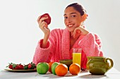 Woman eating fruit in dressing gown