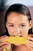 Ein Mädchen beisst in einen Maiskolben