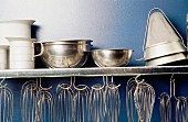 A kitchen shelf with egg whisks and bowls