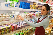 Woman stocking supermarket shelves