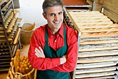 Baker in bakery with trays of baguettes