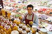 Supermarket sales assistant behind shelf of fruit
