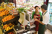 Supermarket sales assistant weighing fruit
