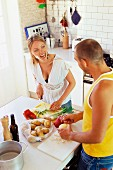 Couple in kitchen peeling potatoes and chopping vegetables