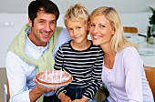 Father, mother and son celebrating birthday with cake