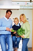 Father, mother and son in kitchen with lettuce and vegetables