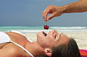 Woman being fed cherries on beach