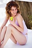 Woman in underwear holding apple
