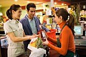 Couple shopping in supermarket standing at till