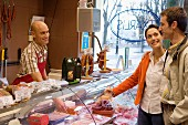 Couple at butchers buying cold cuts