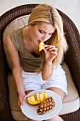 Blond woman, seated, eating a pineapple
