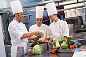 Three chefs preparing vegetables in a commercial kitchen