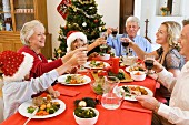 Family toasting each other over Christmas dinner