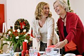 Mother and grown-up daughter setting a table for Christmas dinner