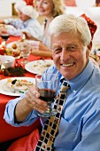 Grandfather at Christmas dinner with glass of red wine