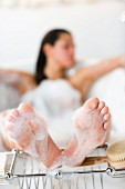 Feet of a woman lying in a bathtub