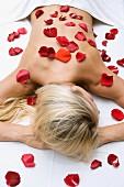 Blonde Frau liegend mit Rosenblütenblätter auf ihrer Haut