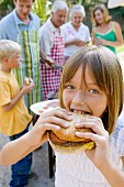 Girl biting into whole home-made burger