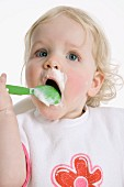 Little girl eating mush from plastic spoon