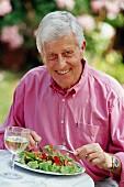 Älterer Mann beim Salat essen