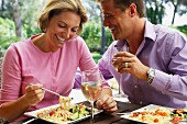 Couple eating lunch of salad and pasta on holiday
