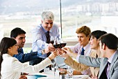 Toasting each other with red wine at a business lunch