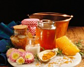 A still life featuring honey, sugar, jam, honeycomb and pollen