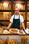 Shop assistant in bakery with pastries and baguettes