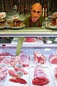 Shop assistant behind counter of butcher's shop
