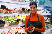 Shop assistant in front of fruit racks