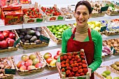 Sales assistant in front of fruit racks with crate of strawberries