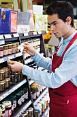Sales assistant in front of shelf of preserves