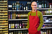 Sales assistant in supermarket in front of shelves of oil and vinegar