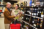 Couple in wine department of supermarket