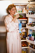 Woman in dressing gown drinking milk in front of open refrigerator