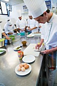 Chefs in a commercial kitchen preparing salad and slicing eggs