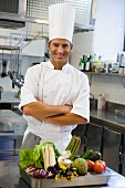A chef with vegetables in a large kitchen