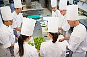 Chefs podding peas in a commercial kitchen