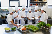 Chefs with orders and vegetables in a commercial kitchen
