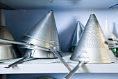 Several pointed sieves on a shelf