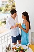 Paar macht im Urlaub Frühstück auf dem Balkon