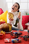 Woman at Christmas holding a piece of panettone & bottle of sparkling wine