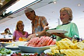 Father with children at fruit buffet