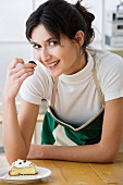 Woman in apron eating slice of cake