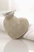 White heart-shaped stone and a feather