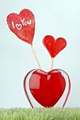 Lollipops in heart-shaped glass vase