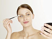 Woman with an eye shadow brush