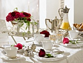 Breakfast table decorated with red roses